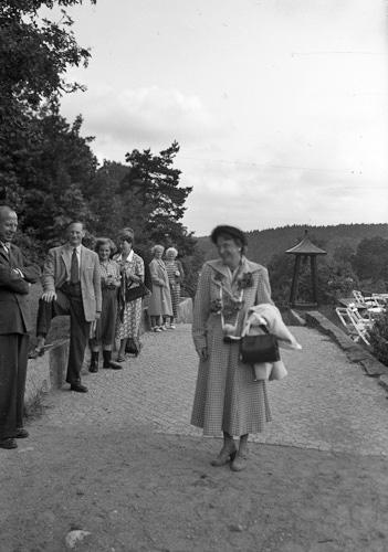 En kvinna står på en trädgårdsgång. Till vänster syns flera människor. I bakgrunden skymtar en trädgård med trädgårdsmöbler.