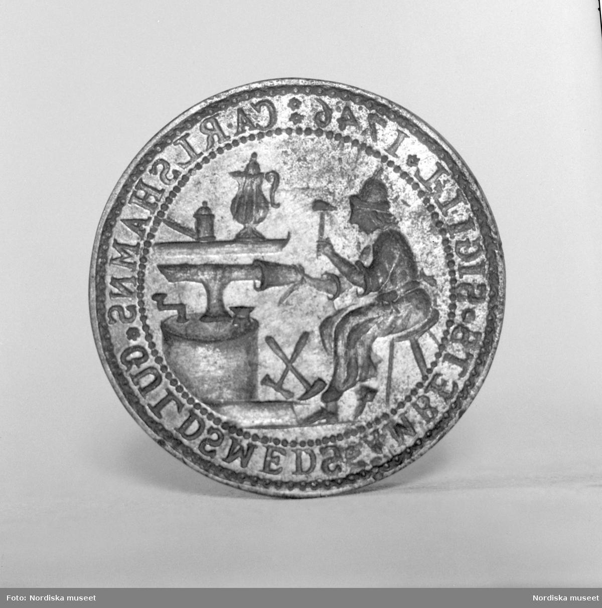 Sigillstamp av järn från 1746 som tillhört Karlshamns guldsmedsämbete. På stampen graverat en man sittande vid ett städ hamrande på en bägare. Runt kanten texten CARLSHAMNS GULDSMEDS ÄMBETS SIGILL 1746.