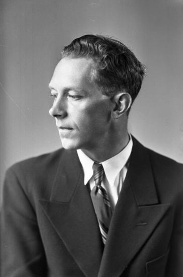 Foto av en man i mörk kostym med slips.Bröstbild, halvprofil. Ateljéfoto.Kan ev. vara: Bror Johan Lennart Johansson (1911-1994), Alvesta.Källa: Sveriges Dödbok 1901-2009.