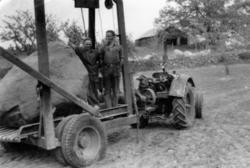 Foto av två män som står på en åker bredvid en stenvagn, för