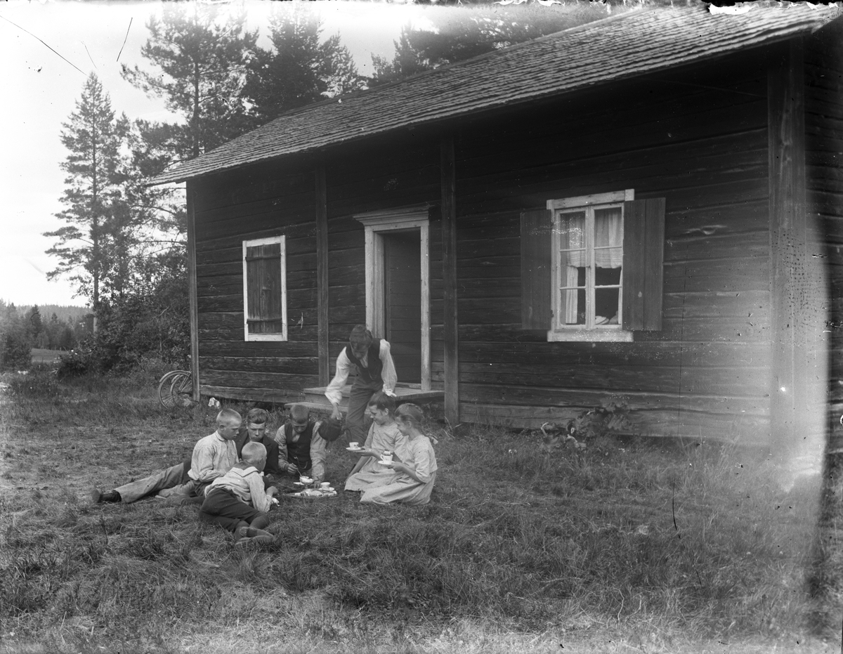 Barn dricker kaffe i gräset utanför hus.