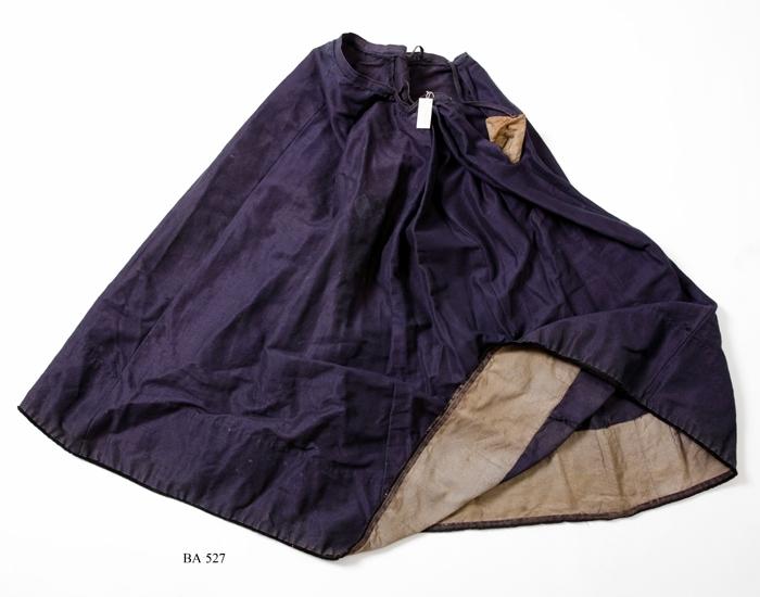"""Mörkblå kjol med fem våder, vävt i korskypert av viktoriagarn. 2 hankar i linningen. 170 mm bred fodring nertill på insidan. Våderna starkt rynkade, med ett sprund mellan två av dem samt med en insydd ficka. Nertill en smal luddig svart kant. Troligen vaxat tyg.   """"Skört"""" av viktoriatyg, vävt av min syster Anna 1883. Tillhört min syster Anna""""   Uppgiftslämnare: dels skriftligt av Blenda Andersson själv och muntligt av Gustav Johannesson f. 1866, anställd hos Blendas far, Anders Jonsson (1828-1902) , på Skörda Lillegård från 1890-talets början och sedan hos Blenda Andersson. Flertalet av föremålen härrör från Skörda Lillegård."""