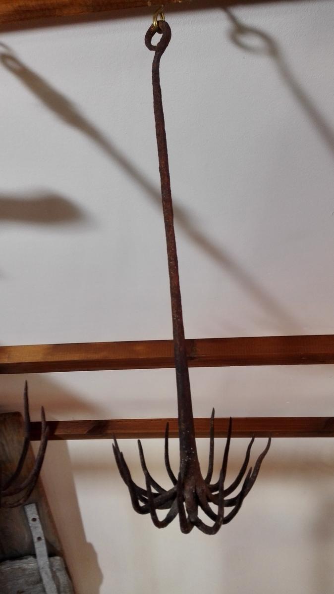 1 spjutedregg.  Konf 4337. Nærværende har 14 tinder. Leggen, der ender i en rund løkke øverst, er 37 cm lang. Gave fra Ole J. Rinde, Feios.
