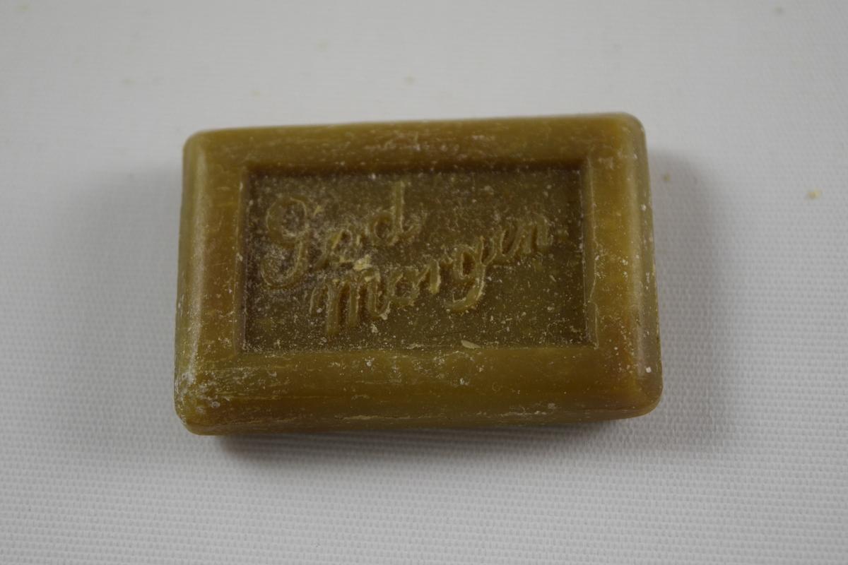 """Rektangulær såpe, grønn, tre like såper (A, B, C) produsert på Saanums Sepefabrikk i Mandal. Rektangulær fordypning med relieffteksten """"God morgen!"""" på overside og """"Saanum Mandal"""" på underside."""