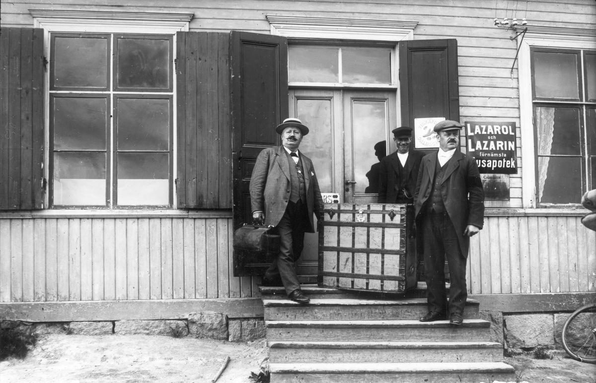 Utanför Perssons affär i Voxsätter omkring 1915. Ingången till butiken fanns då på husets långsida. Från vänster: Sylvestersson från Bollnäs, handlare Per Persson, obekant. Herrarna var resande för Zimmermans skofirma i Gävle.