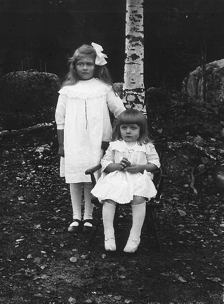 """Gunborg Larsson (född Lindberg, Hällbo) och Ingrid Falk sittande på """"Berget"""" i Östansjö."""