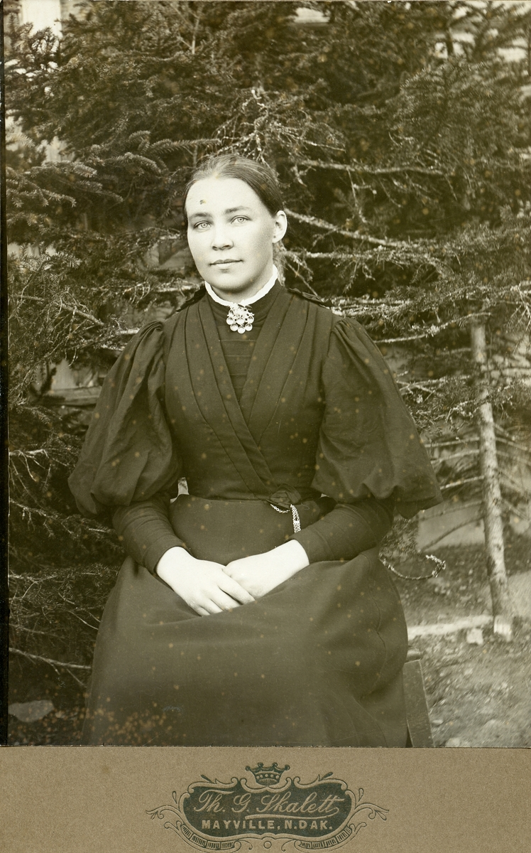 Portrett av ung kvinne. Hun sitter på en stol foran noen grantrær og er kledd i en mørk kjole. kjolen har hvit halskant og hun har en sølje i halsen.