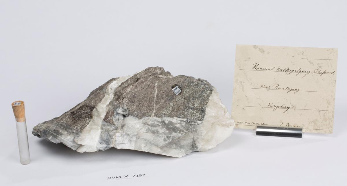 Eske inneholder et glassrør med litt hvitt pulver  Etikett på prøve: 11-gang Nær «Raata» 295 Samuel  Kgb  Etikett i eske: Normal kalkspatgang. Sølvførende nær Raatagang Kongsberg C. Bugge