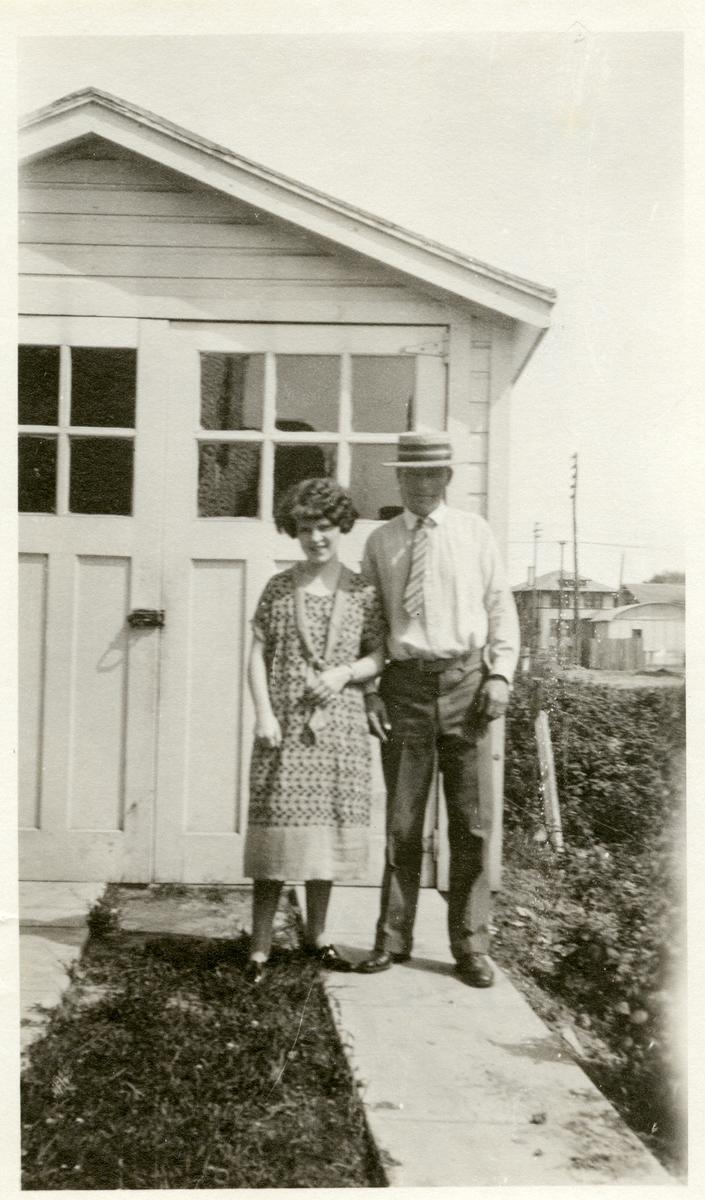 Mann og kvinne avbildet utenfor en garasje