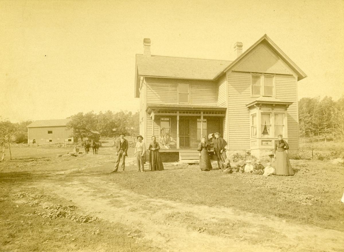 Flere kvinner, menn og barn er avbildet utenfor et hus på en farm i Amerika. I bakgrunnen er det en låve. Nr to fra venstre er Pål Milevatnet.