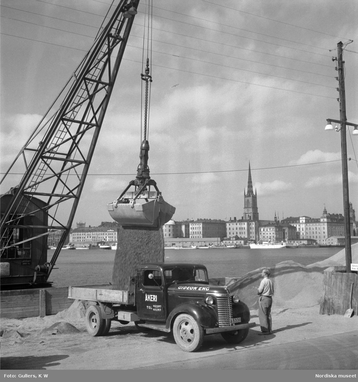 En lastbil med lastas med sand på kajen vid Söder Mälarstrand, Stockholm.