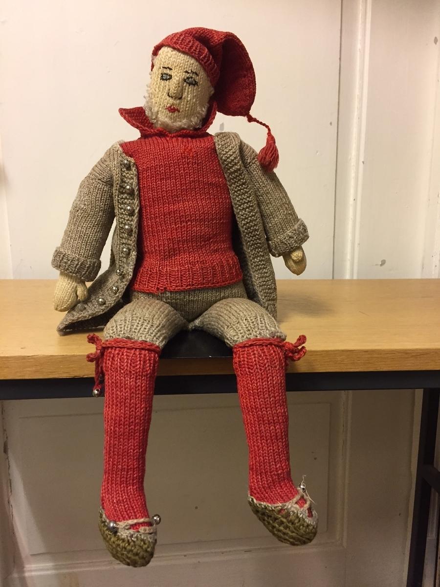 Dukke med nissaktig utseende. Hard, polstret kropp med strikkede klær. Øyne, øyenbryn, munn og nesebor er sydd på. Kulrerunde metallknapper.