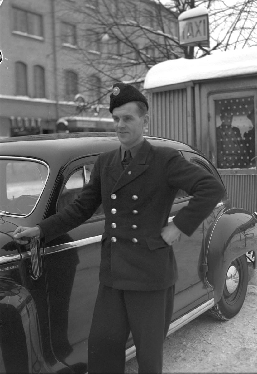 Taxichaufför Stråhle. 14 januari 1949. Reportage för Arbetarbladet. Bilden är tagen på Stortorget, inte Centralplan, med biografen Roxy i bakgrunden.