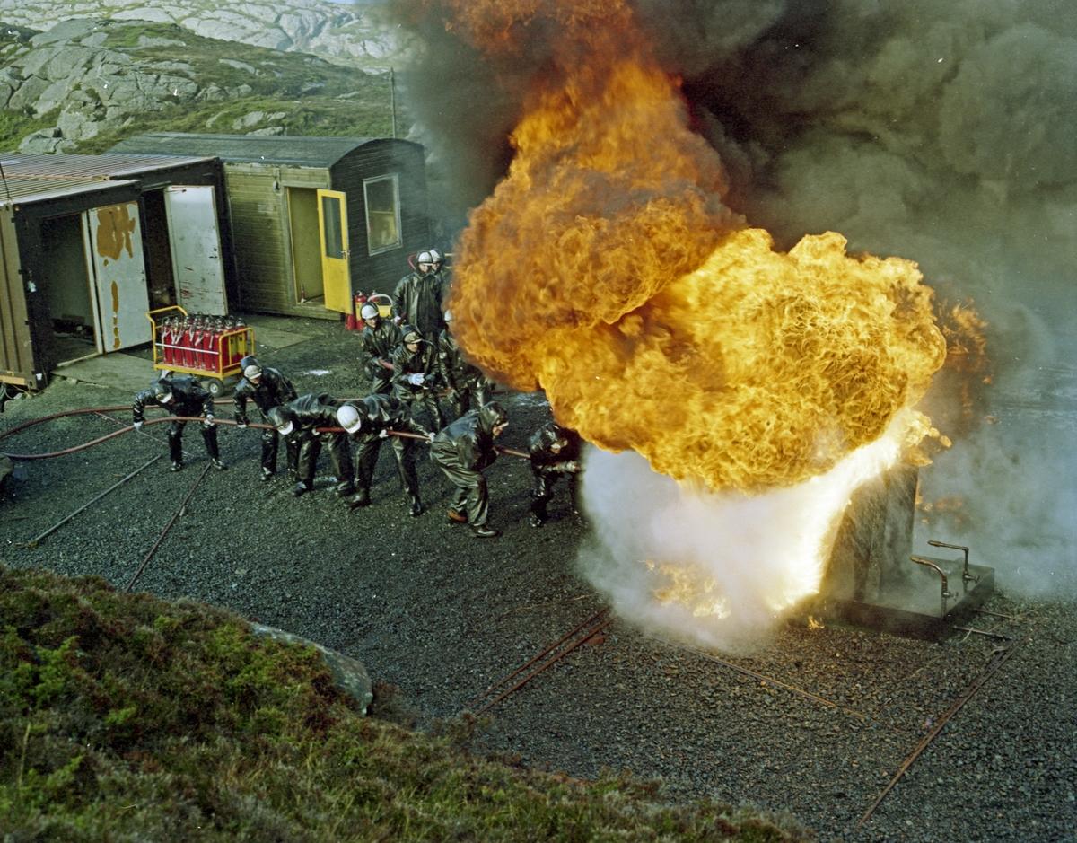 H.M.V. Brannslukking. Flere personer i oljehyre som trener på å slukke en oljebrann.