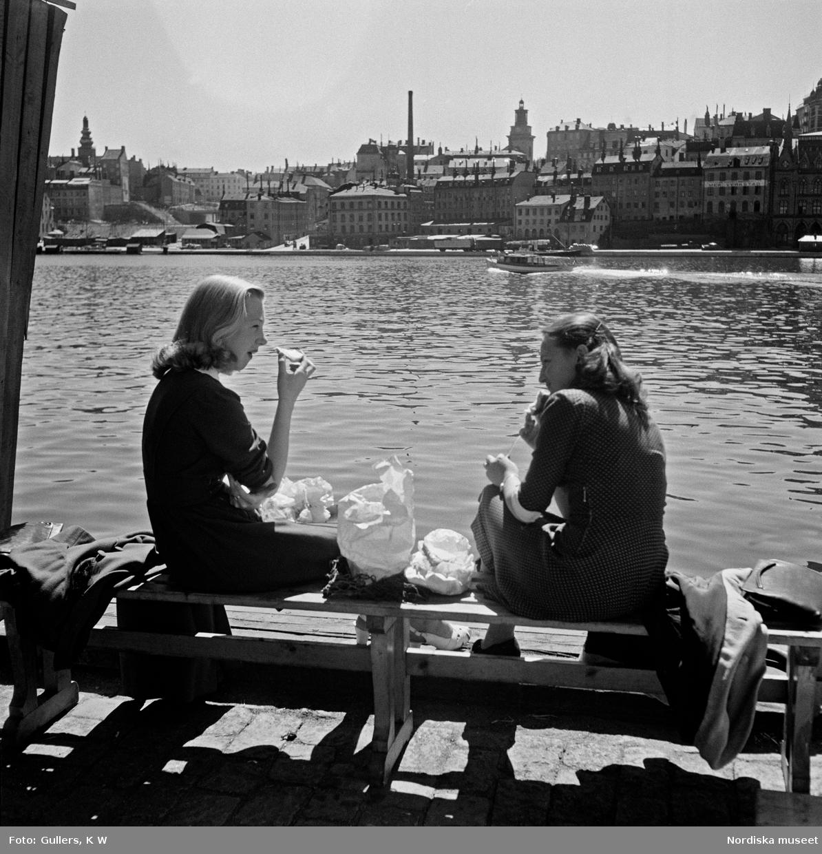 Två kvinnliga kontorister äter sin lunch vid kajen vid Södra Riddarholmshamnen, Stockholm. I bakgrunden Riddarfjärden och bebyggelse på Södermalm.