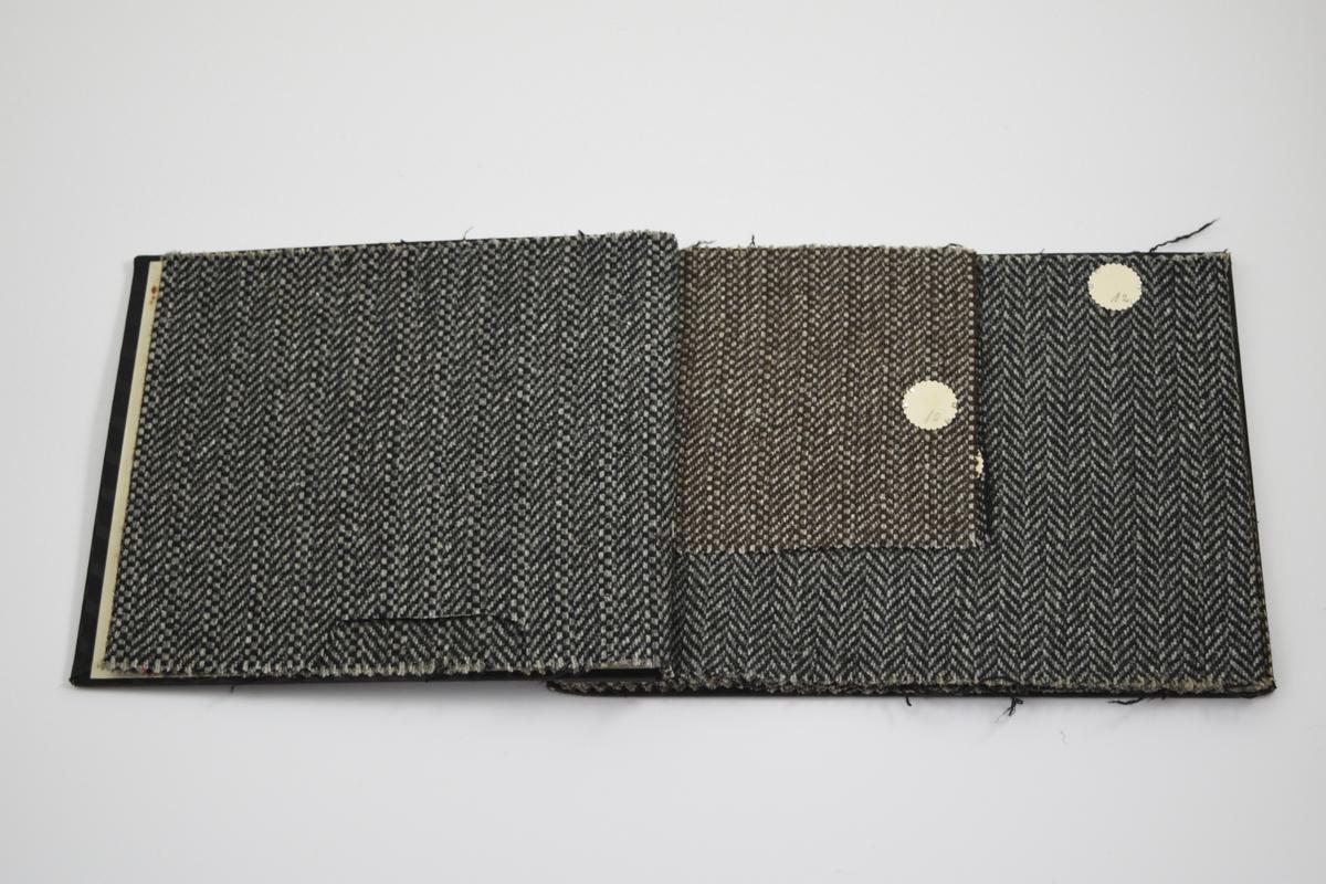 """Prøvebok med 7 prøver. Middels tykke stoff med ulike fiskebensmønster eller lignende. Stoffene ligger doblet i boken, noen er klippet til et mindre format og ligger enkelt. Stoffene er merket med en rund papirlapp, festet til stoffet med metallstifter, hvor nummer er påført for hånd. Påskriften på innsiden av forsideomslaget viser at alle stoffene har kvalitet """"Alf"""".   Stoff nr.: alf/9, alf/10, alf/11, alf/12, alf/13, alf/14, alf/15."""