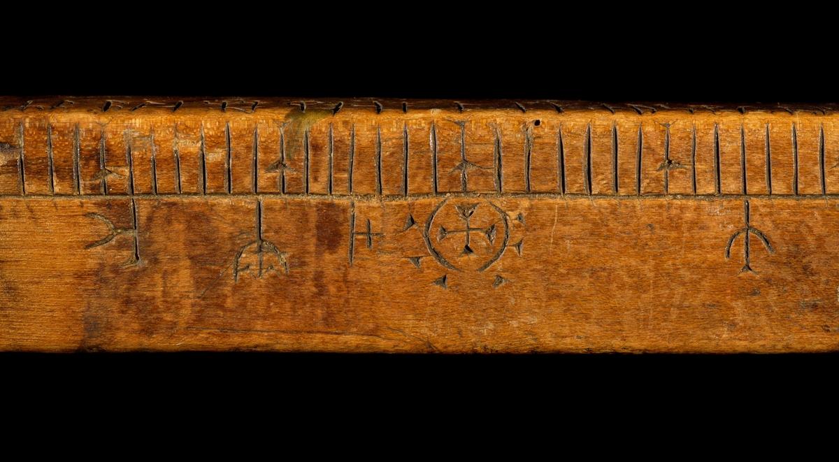 Kalenderstav i form av en svärdsformad runkalender. Av björk med rektangulärt genomsnitt och snidat handtag. Bränd i nedre änden. Runstaven är av ålderdomlig typ, saknar nästan helt symbolbilder.