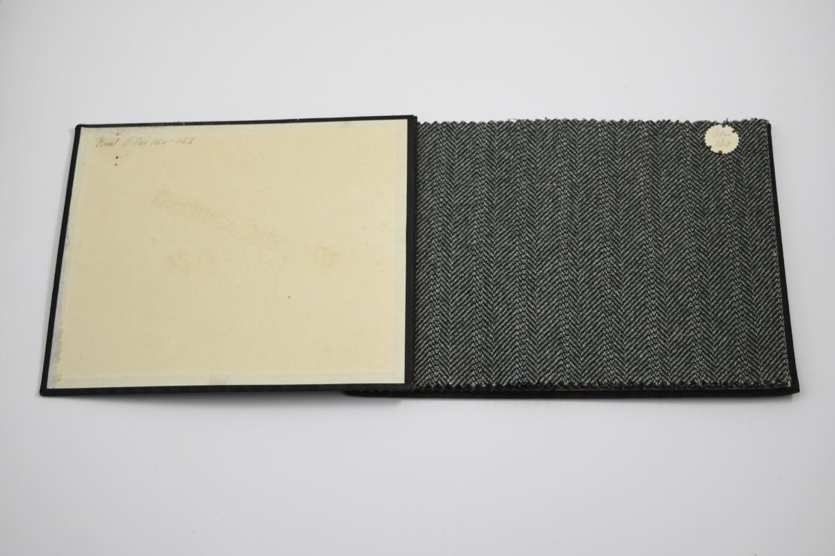 """Prøvebok med 3 prøver. Middels tykke stoff med blant annet fiskebensmønster - mønsteret er tilnærmet likt på forsiden og baksiden av stoffet. Vevemønsteret er likt for alle prøvene, men er speilvendt på den første prøven. Fargenyansen varierer. Stoffene ligger brettet dobbelt i boken. Stoffene er merket med en rund papirlapp, festet til stoffet med metallstifter, hvor nummer er påført for hånd. Innskriften på innsiden av forsideomslaget viser at alle stoffene i boken har kvaliteten """"Olav"""".   Stoff nr.: Olav/150, Olav/151, Olav/152."""