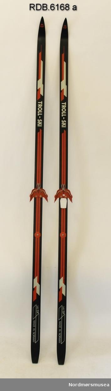 Et par svarte glassfiberski med rød og kvit dekor. Svart såle. Påmontert røde rottefellabindinger med sølvfarga bøyle, kvite fotplater og røde, åttekanta hælplater av plast.