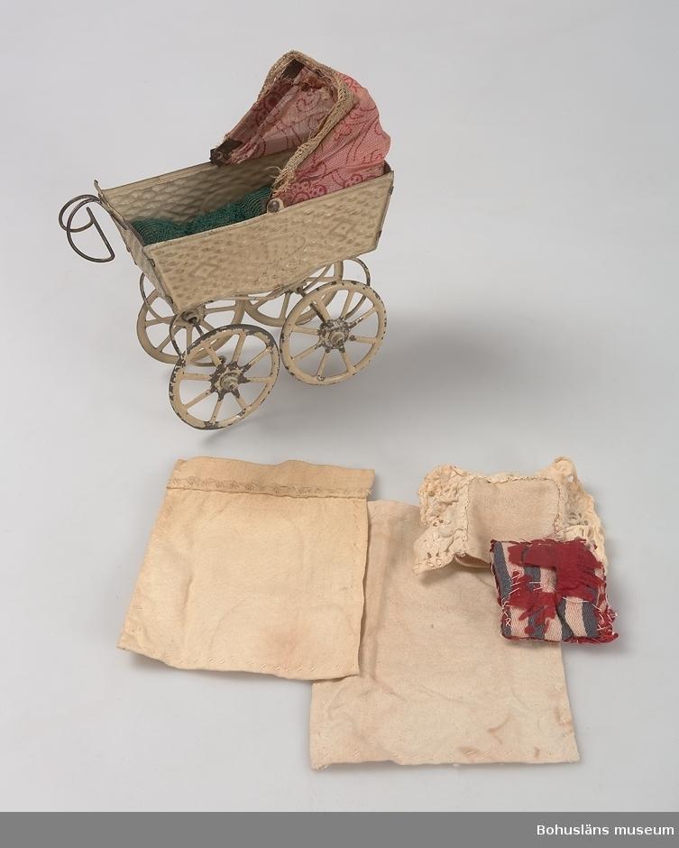 """OBS endast sängkläderna tillverkade av systrarna Bohlin.  Dockvagn av pressad plåt, korgen skall ge intryck att vara flätad, hjul med ekrar, två fjädrar av järntråd mellan axlar och korgen. Beige. Suflett av rosa genomskinlig textil med röda blommor. Färgen avsliten på flera ställen. Snarlik UM023811. Sängkläderna består av: 1 st. madrass i grönt, 1 st underlakan, 1 st. överlakan samt kudde med örngott. Örngott märkt """"Gösta"""" med gul tråd."""