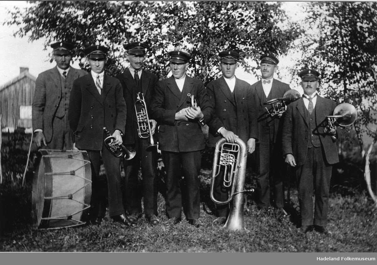 Lunner musikkforening. Korpsmusikere står oppstillt ute foran noen løvtrær
