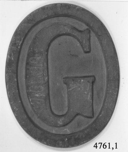 Stävmärke, modell. Av trä. Utgör en oval, gulmålad bricka med bokstaven G. Märkt på framsidan: 6339,7 och på baksidan med bläck: 2 st. av mässing till Götas Båtar.