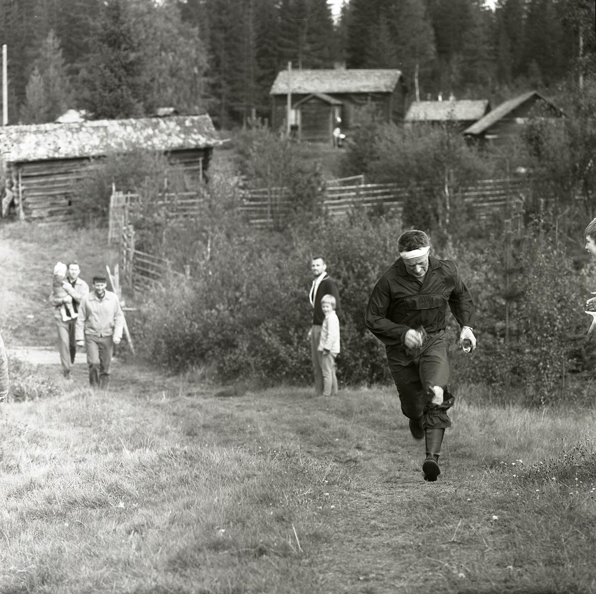 En man kommer springande upp för en backe i Svartbo 1963. Han deltar i distriksmästerskapen i orientering och en liten publik bestående av barn och tre män hejar på honom. I bakgrunden står ett fäbodlandskap med gärdesgårdar, stugor och åkermark.