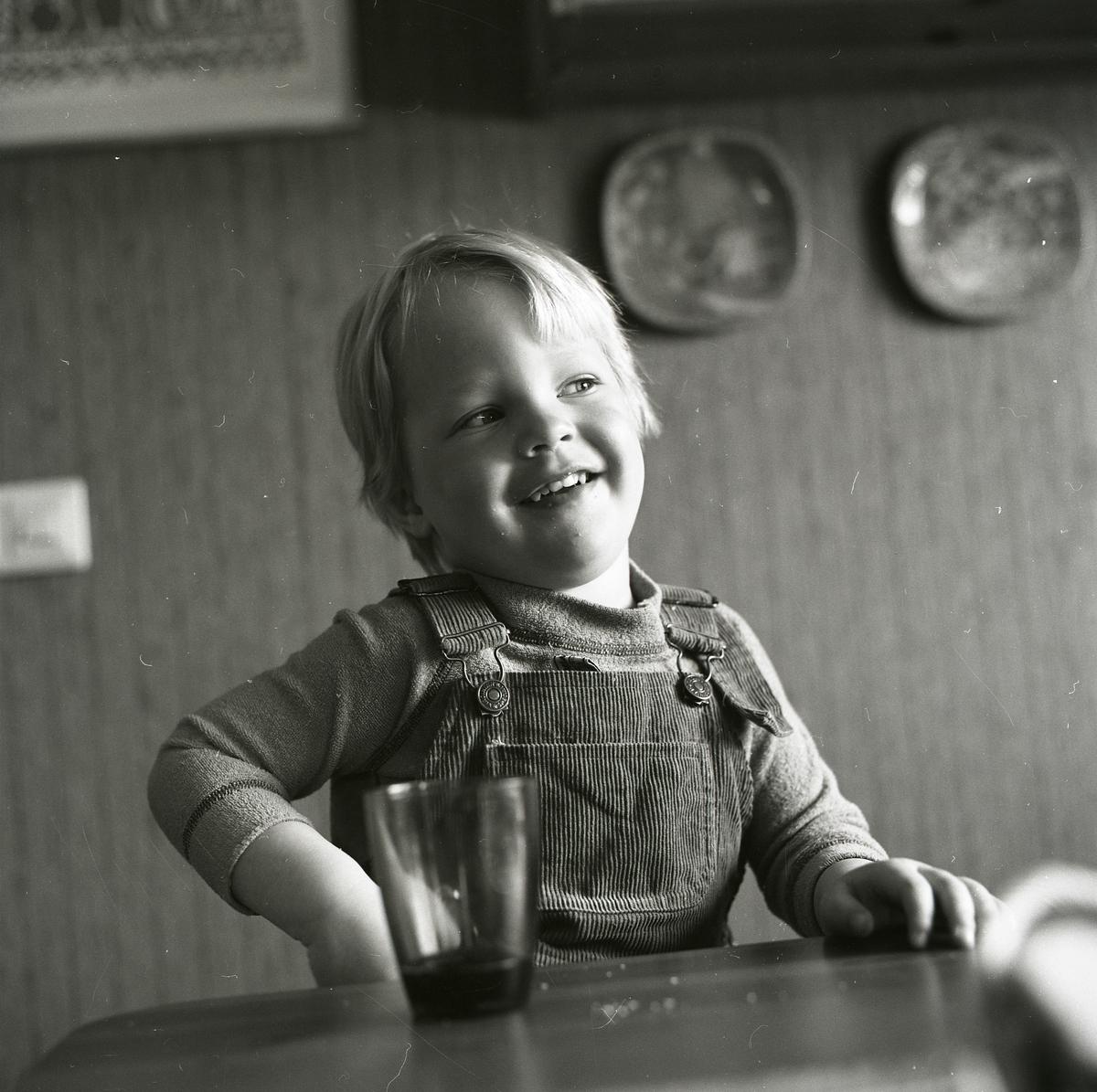 En pojke klädd i hängselbyxor sitter vid ett bord och ler. Han har ljust hår som faller ned och skuggar pannan. Han observerar något utanför bilden och hans min är glad och busig. Med sin ena arm verkar pojken vara på väg att sträcka sig efter vattenglaset på bordet framför honom.