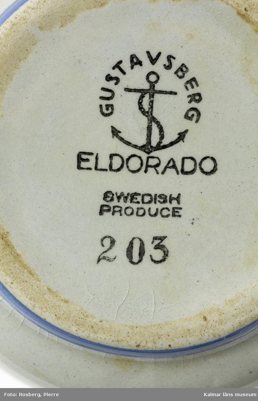 KLM 28730:7 Gräddkanna, av blåtonad pyromassa. Modell Eldorado, Gustavsberg. Liten kanna av gråtonat gods, fotringen oglaserad. Enkel rågodsmålad dekor i rutmönster i blått och svart. Stämpel med svart färg, Gustavsberg (kring ett ankare) ELDORADO Swedish produce 203.