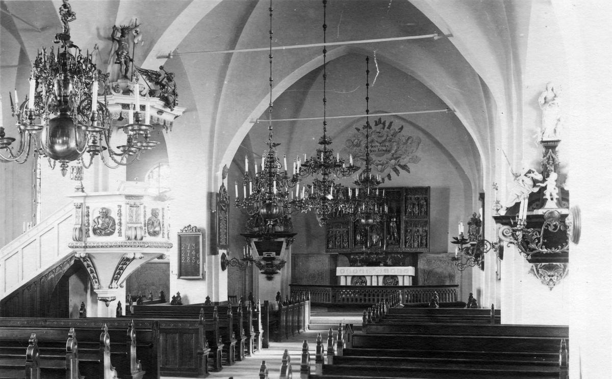 Interiör från Köpings kyrka. Mittgången med predikstol och altarskåp.
