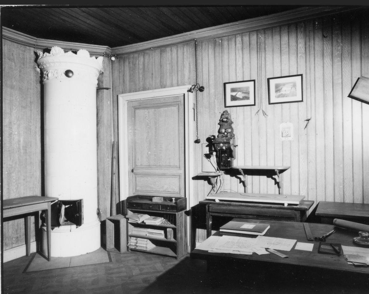 Gamla brukskontoret, Inspektorrummet.  Kakelugn, 3 st. bord 1 st. hylla, 1 telefon 2 st. fotografier på ålkaren på dammen, dörr till lägenhet (kyrklängan).