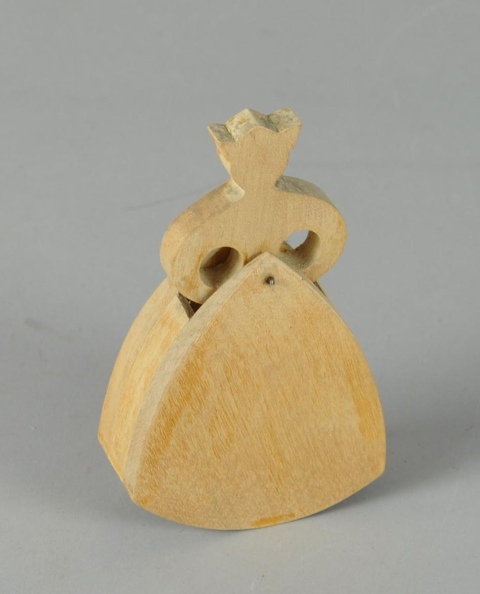 Figur av tre, formet som dame i kjole. Figuren består av 2 lag med tre - en avrundet trekant med åpning på topp og bunn, og en overkropp som er satt inn i den øverste åpningen. Overkroppen er festet til trekanten med spiker, og kan vendes til sidene. Damen har en krone på hodet.