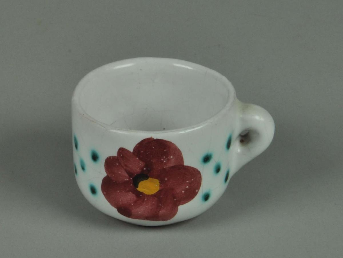 Keramikkopp med hvit glasur og påmalt blomstermotiv.