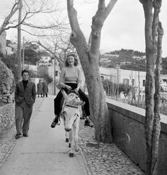 En flicka som rider på en åsna och en man går bredvid med hä