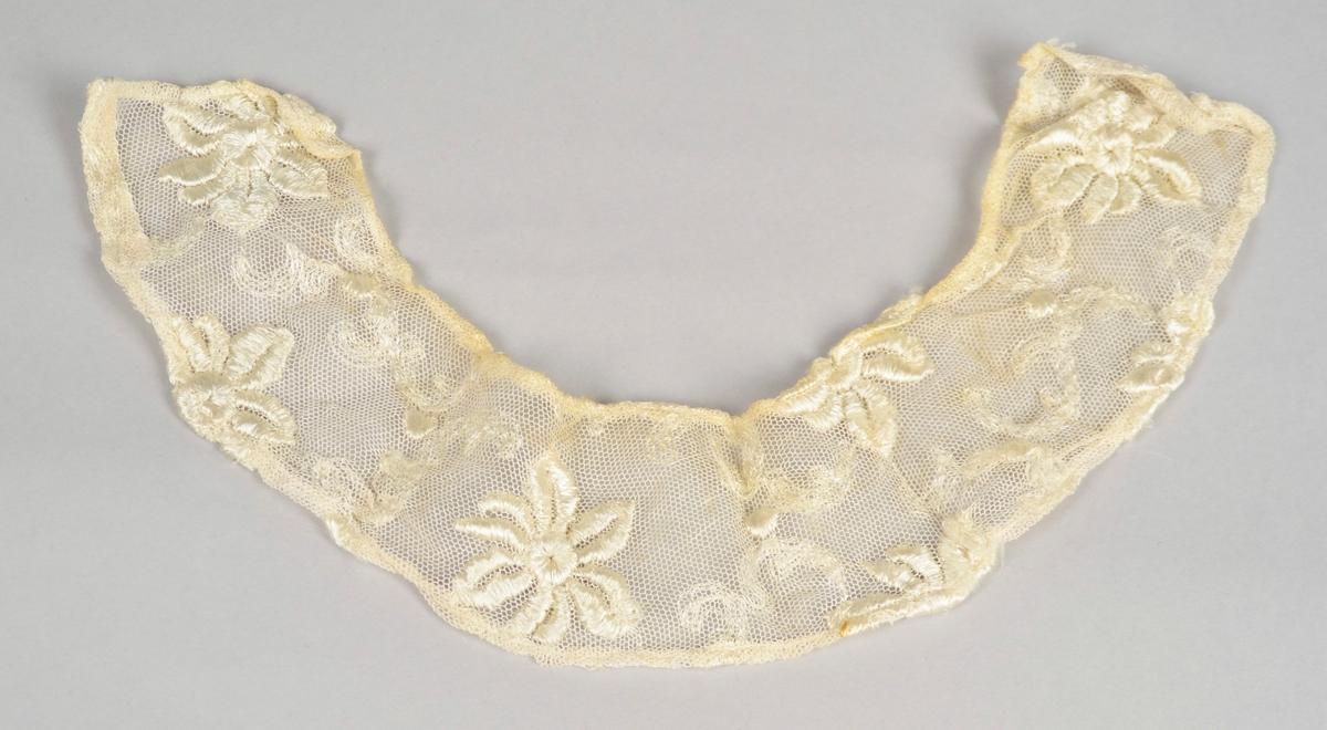 """Blondekrage. Blomemønster i silkeaktig tråd på gjennomskineleg stoff med store """"maskar""""."""