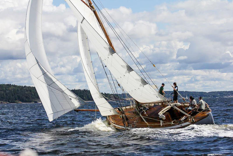 Skøyta S/Y Venus i vannet, tre seil, fire personer ombord. I bakgrunnen utsikt til skog.