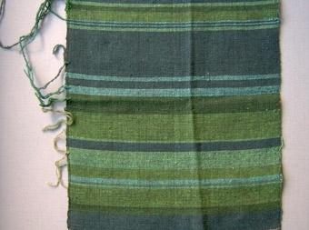 Detta vävprov är vävt i tuskaft med en svart bomullsvarp. Provet har en oregelbunden randning i olika gröna och blågröna nyanser. Garnprover fästa på provet.
