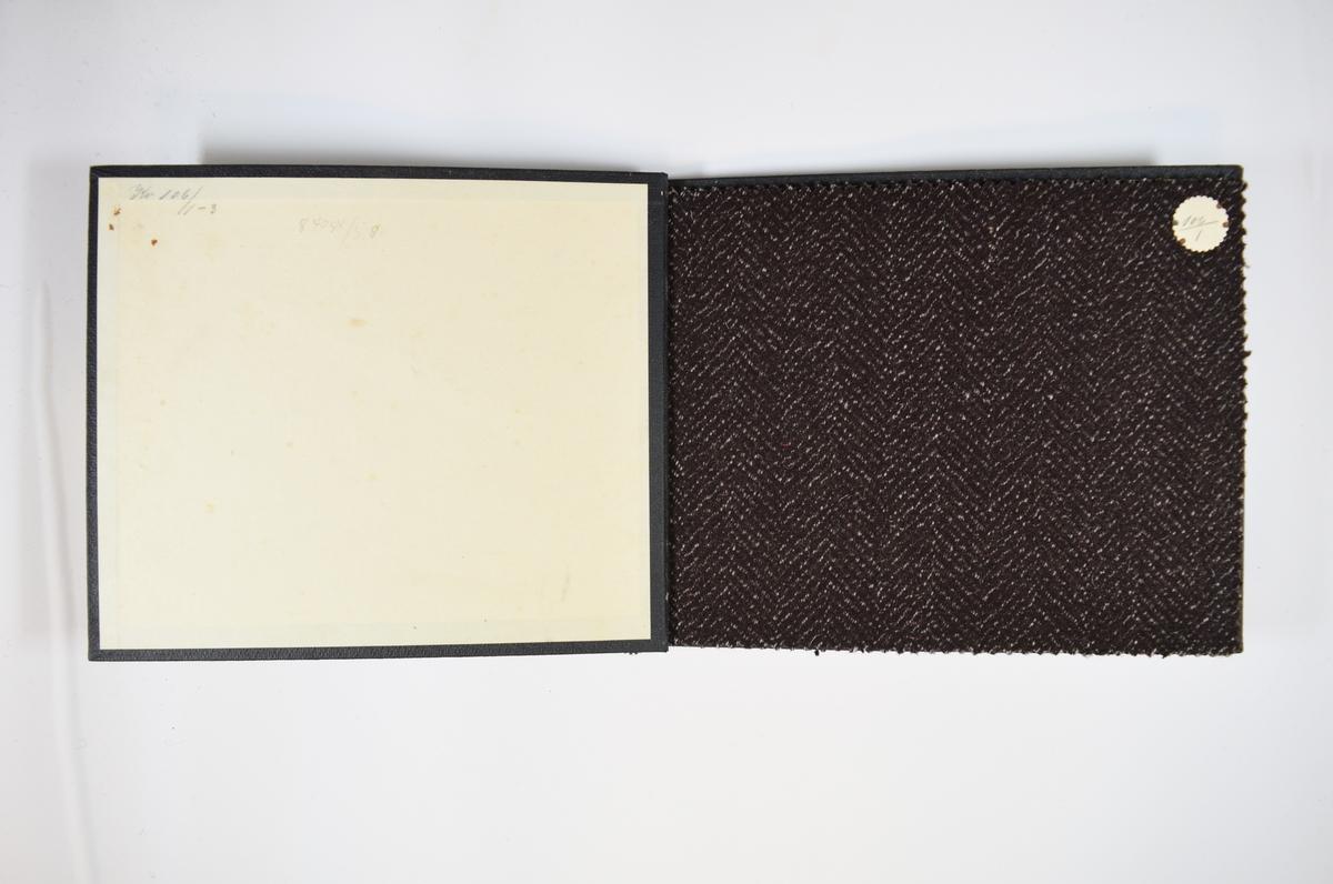 Prøvebok med 3 stoffprøver. Middels tykke stoff med diskret fiskebensmønster. Stoffene er merket med en rund papirlapp, festet til stoffet med metallstift, hvor nummer er påført for hånd. Innskriften på innsiden av forsideomslaget indikerer at alle stoffene har kvalitetsnummer 106.   Stoff nr.: 106/1, 106/2, 106/3.