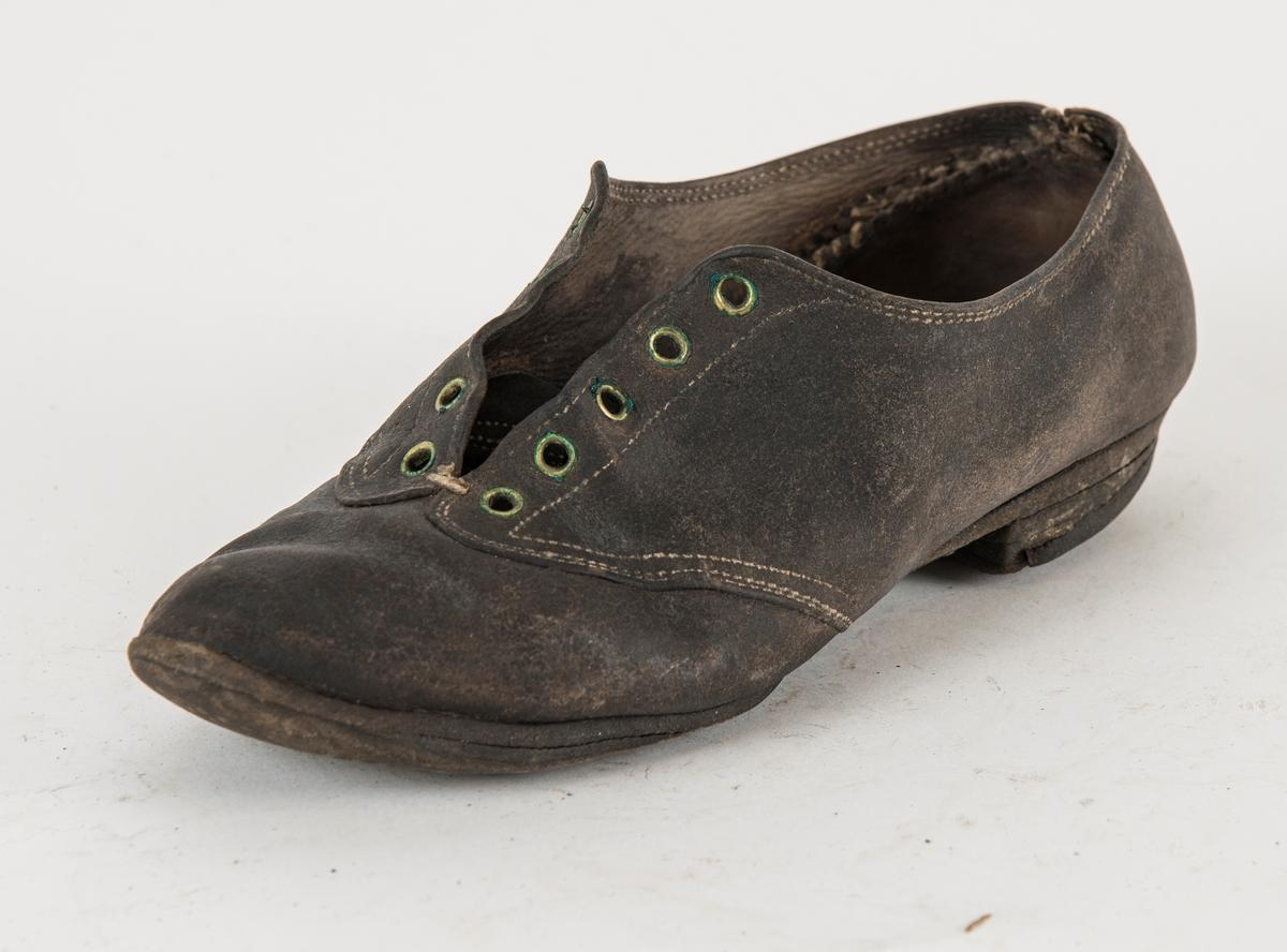 Snøresko i brunt skinn med fem par maljer.  Heimelaga pluggsko. Låg hæl. Venstre fot. Ufóra.