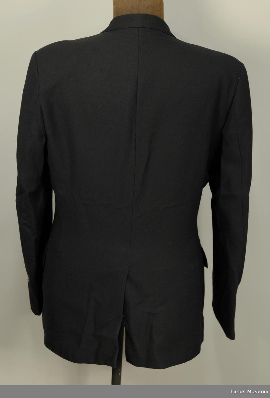 Enkeltspent med 4 blanke knapper. 2 smale kvite striper på kvart erme med elastisk bånd. Brystlomme på kvart forstykke, utanpåsydde med klaff og blank knapp og fold på midten.