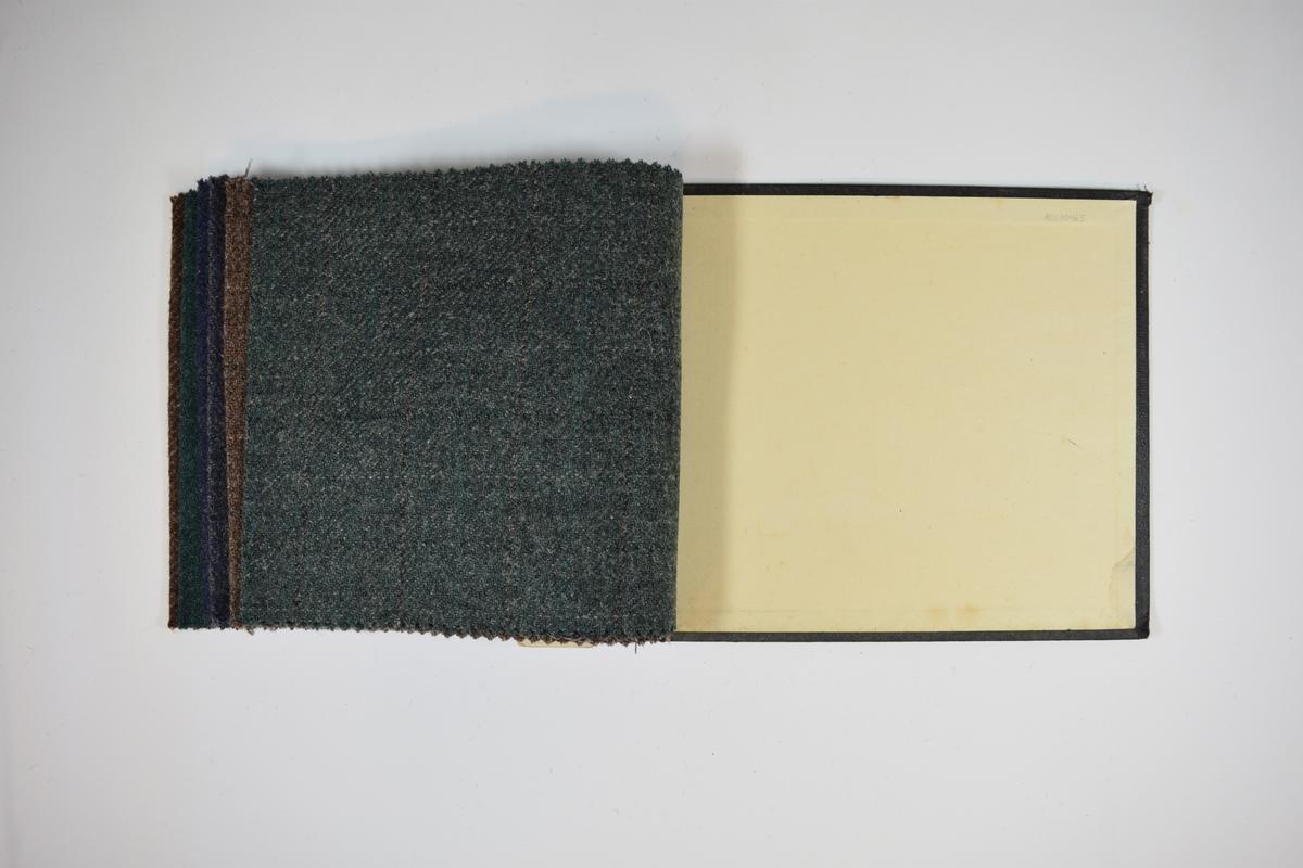 Prøvehefte med 6 prøver. Middels tykke stoff med diskret rutemønster. Stoffene ligger brettet dobbelt i heftet. Stoffene er merket med en rund papirlapp, festet til stoffet med metallstifter, hvor nummer er påført for hånd. Heftet har stiv bakplate og en papp-plate der heftet er stiftet som dekker ca. 5 cm forsiden. På pappen på forsiden er det en innskrift som indikerer at alle stoffene har kvaliteten 167B.   Stoff nr.: 167B/26, 167B/32, 167B/50, 167B/51, 167B/55, 167B/58.