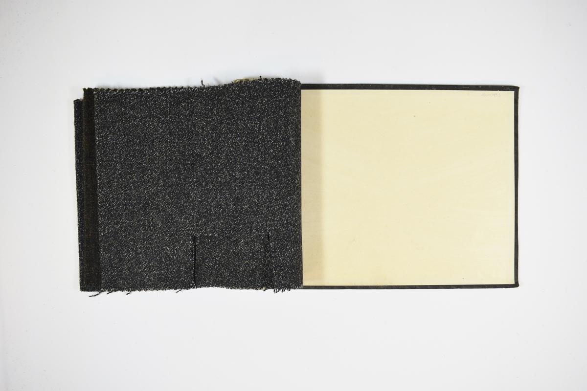 Prøvehefte med 3 prøver. Middels tykke stoff med prikkemønster. Stoffene ligger brettet dobbelt i heftet. Stoffene er merket med en rund papirlapp, festet til stoffet med metallstifter, hvor nummer er påført for hånd. Heftet har stiv bakplate og en papp-plate der heftet er stiftet som dekker ca. 5 cm forsiden.   Stoff nr.: 500/1, 500/2, 1490.