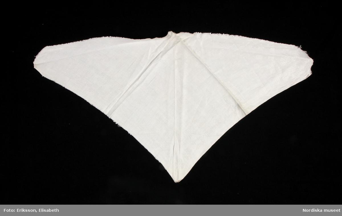Halskläde i vit damast med fornnordiskt mönster. Tresnibb med stadkant på ena kortsidan, andra kortsida och långsida klippt kant.