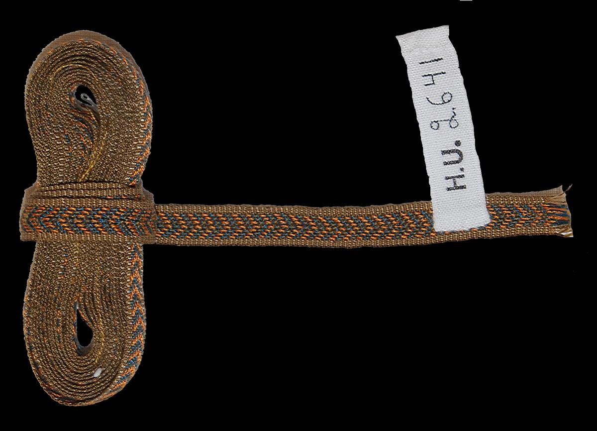Band 204 x 0,8 cm. Merceriserad bomull, ripsvävd botten. Brungul botten med viggar i blått och orange i nubben.  Katalogiserad av Karin Nordenfelt, Elisabet Stavenow, Marie-Louise Wulfcrona-Dagel.