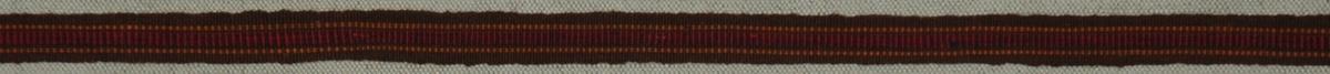 Band 302,5 x 1,2 cm. Bomull, ripsvävt. Två gula smala ränder, en bred blåröd rand.  Katalogiserad av Karin Nordenfelt, Elisabet Stavenow, Marie-Louise Wulfcrona-Dagel.