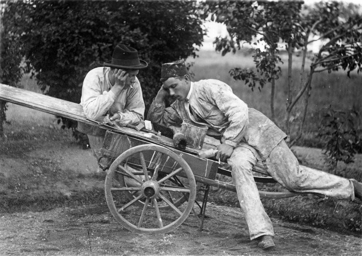 Målarlärlingar sitter på 2-hjulig kärra