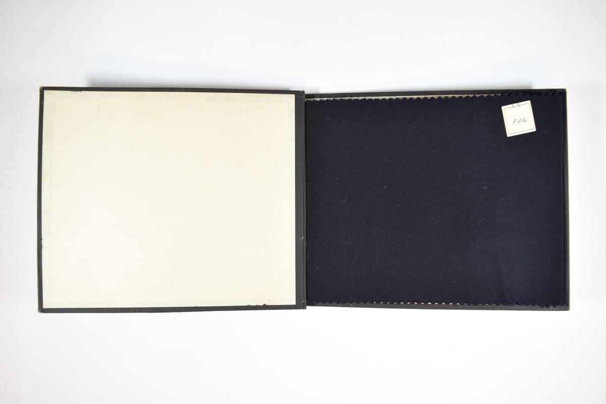 Prøvebok med 6 stoffprøver. Relativt tynne ensfargede mørkeblå stoff med kyperbinding/diagonalvevd. Tykkelsen på tråden varierer mellom stoffene, ellers er de svært like. Alle stoffene har ulike kvalitetsnummer (designnummer er ikke oppgitt). Trolig er boken laget for å sammenligne disse små forskjellene mellom kvalitetene. Stoffene ligger brettet dobbelt slik at vranga skjules. Stoffene er merket med en firkantet papirlapp, festet til stoffet med metallstifter, hvor nummer er påført for hånd.   Stoff nr.: 726, 727, 729, 1000, 4500/blå, 4600.