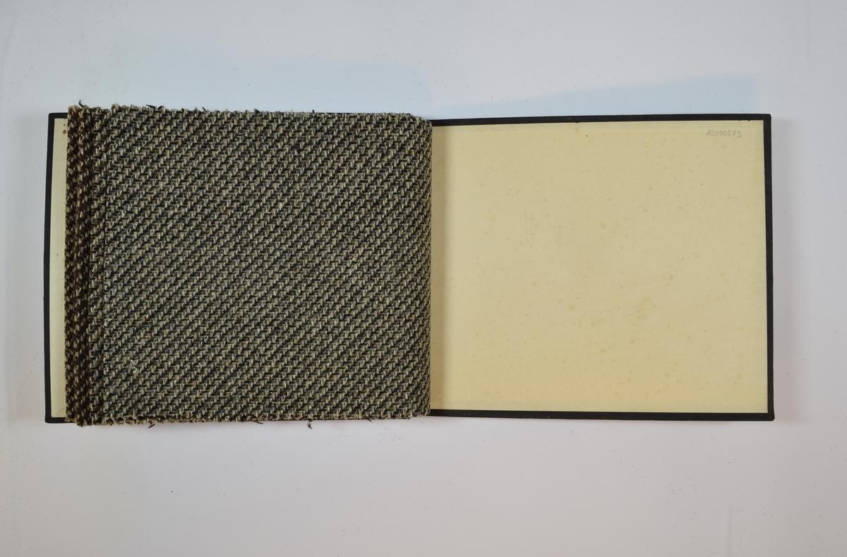 Rektangulær prøvebok med 4 stoffprøver. Middels tykke stoff med skrå striper. Kyperbinding/diagonalvevd. Fargen på stoffene varierer. Stoffene ligger brettet dobbelt i boken slik at vranga dekkes. Stoffene er merket med en rund papirlapp, festet til stoffet med metallstifter, hvor nummer er påført for hånd. Alle numrene er krysset over med rød fargeblyant. Påskriften på innsiden av forsideomslaget indikerer at alle stoffene har kvalitetsnummer 1850.   Stoff nr.: 1850/70, 1850/71, 1850/72, 1850/73.