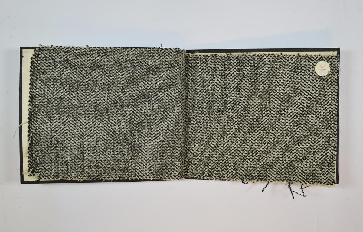 Rektangulær prøvebok med 4 stoffprøver og harde permer. Permene er laget av hard kartong og er trukket med sort tynn tekstil. Boken inneholder middels tykke melerte stoff med ulike fiskebensmønster. Både farger og mønster varierer mellom stoffene. Stoffene er merket med en rund papirlapp, festet til stoffet med metallstifter, hvor nummer er påført for hånd. Innskriften på innsiden av forsideomslaget indikerer at alle stoffene har kvalitetsnummer 1975.   Stoff nr.: 1975/1, 1975/3, 1975/4, 1975/5.