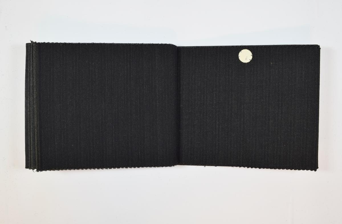 Rektangulær prøvebok med 9 stoffprøver og harde permer. Permene er laget av hard kartong og er trukket med sort tynn tekstil. Boken inneholder middels tykke, mørke stoff med diskret striper og/eller fiskebensmønster. Stoffene er merket med en rund papirlapp, festet til stoffet med metallstifter, hvor nummer er påført for hånd. Innskriften på innsiden av forsideomslaget indikerer at alle stoffene har kvalitetsnummer 2000B. En av prøvene (2000B/9) er ikke festet til boken, men ligger løst inni den.   Stoff nr.: 2000B/1, 2000B/2, 2000B/3, 2000B/4, 2000B/5, 2000B/6, 2000B/7, 2000B/8, 2000B/9.